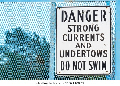 Sign by river warning of strong currents and undertows no swimming
