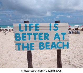 A sign in Cancun, Mexico showing life is better at the beach.  Caribbean ocean sign on the sandy beach.