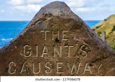 A sign for the Giant's Causeway in Northern Ireland etched into a rock.