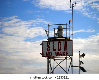 """Sign in channel advising """"Slow, No Wake."""""""