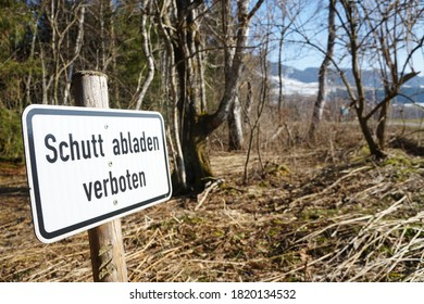Sign close to a wood, saying Unloading rubbish prohibited in german letters. In German it means Schutt abladen verboten