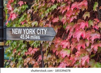 A sign in Cold Spring, NY showing the miles to Manhattan from this village that borders the Hudson River.