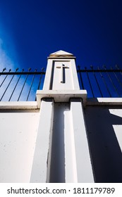 Sign of the cross engraved on the white walls of a cemetery, concept of religious isolation.