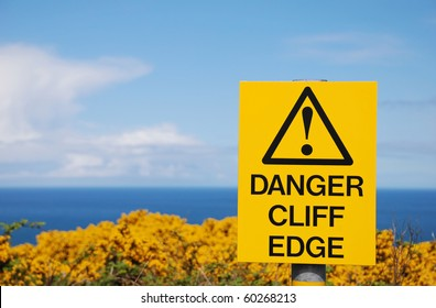 sign danger cliff edge on the Antrim cliffs yellow with goarse in spring