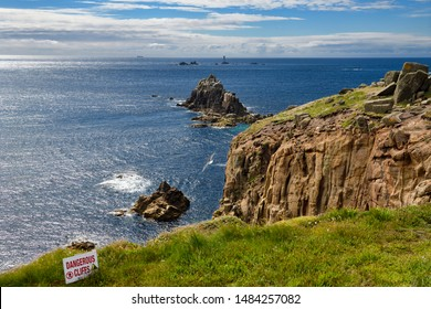 Sign for dangerous cliffs at the edge of Land's End looking to Armed Knight and Longships Lighthouse islands in the Atlantic Ocean Land's End, Cornwall, England - June 12, 2019