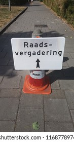 """Sign for direction with dutch text """"raadsvergedering"""" which means """"city council meeting"""" to direct people to temporaty meeting space in secondary school in Zuidplas, the Netherlands"""