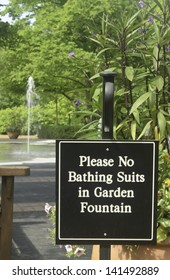 Sign to discourage playing in fountain of formal garden
