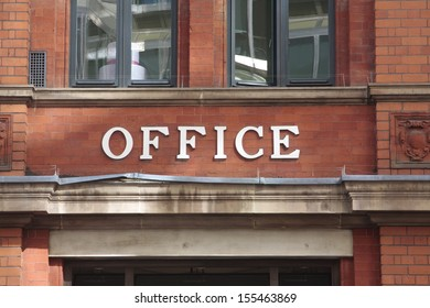 A sign displaying the word office outside of a building