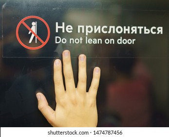 The sign: Do not lean on door (translation). A human palm leaned against the door with the words Do not lean.