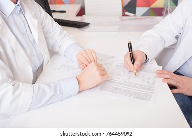 sign documents in medical clinic, close-up of doctor's hand dressed in white uniform