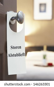 "Sign with Dutch text ""Storen Alstublieft"" (please disturb) hanging on hotel room door"