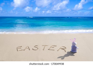 "Sign ""Easter"" with bunny on the sandy beach by the ocean"