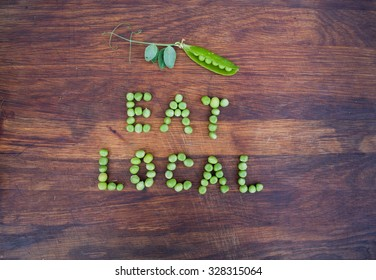 """Sign """"Eat Local"""" made of green peas and pea pod with leaves on wooden background. Organic vegetable produce at a farm."""