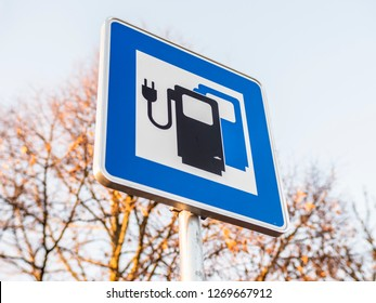 Sign Electric Vehicle charging point on highway parking lot future of personal transportation and refueling