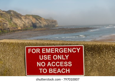 Sign: For emergency use only, no access to beach, with the blurry beach and cliffs in the background, seen at Sandsend Beach, North Yorkshire, UK