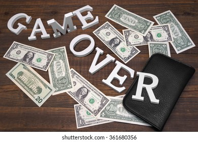 Sign Game Over Dollars And Empty Purse On Wood Background. Concept For  Bankruptcy, Gambling, Fraud, Bribe