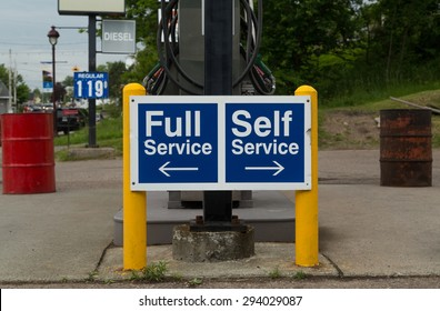 A sign at a gas station instructing people to go to the left for Full Service or the right for Self Service pumps