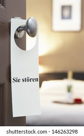 "Sign with German text ""Sie st_ren"" (please disturb) hanging on hotel room door"
