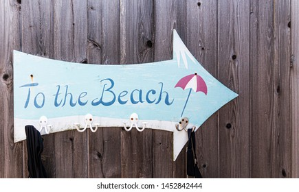 A sign is hanging on a wood wall in the shape of an arrow pointing to the beach and has clips to be a towel holder.