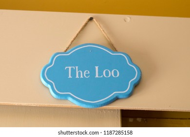 A sign hanging up which says the loo