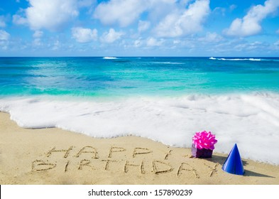 """Sign """"Happy Birthday"""" with decoration on the sandy beach by the ocean"""