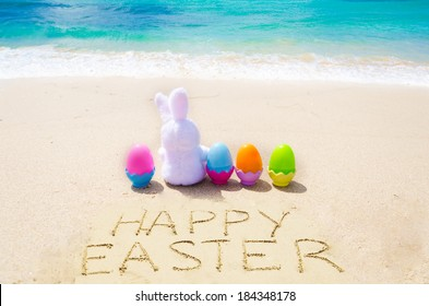 "Sign ""Happy Easter"" with bunny and color eggs on the sandy beach by the ocean"