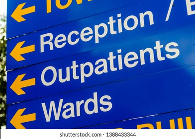 Sign in a hospital directing visitors to reception, outpatients and wards.