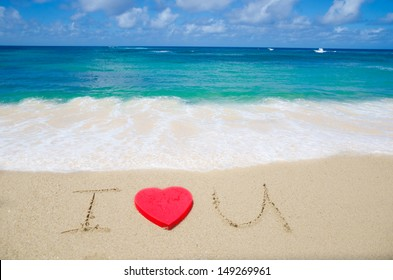 """Sign """"I Love U"""" with red heart shape on the beach"""