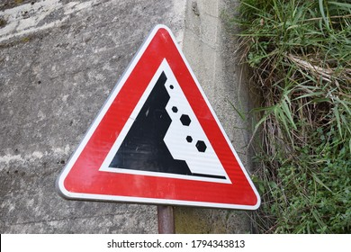 Sign indicating the danger of falling rocks placed in a semi-urbanized area