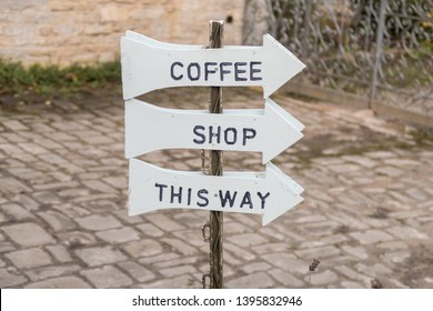A sign indicating the direction of a coffee shop