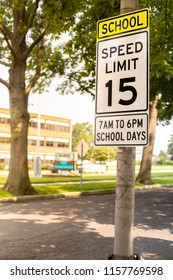 Sign indicating school zone speed limit of 15 miles per hour with school building seen in the background