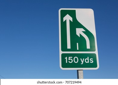 Sign indicating that traffic will merge 150 yards ahead against a clear blue sky with copy space