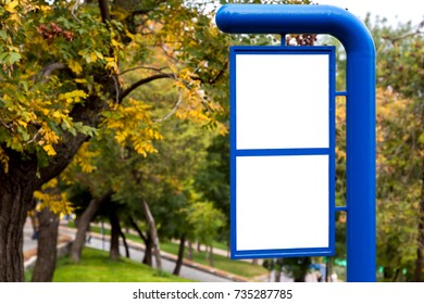 the sign information column, empty with the place for signs and information for pedestrians in the park against the background of trees.