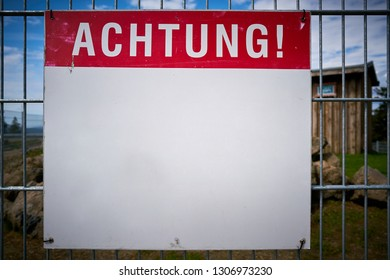 "Sign with the inscription ""Attention"" on a fence"