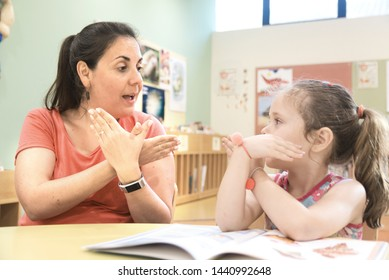 Sign language teacher in a extra tutoring class with a deaf child girl using American Sign Language.