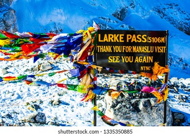The sign of the Larke Pass 5106 meters high peak at the Manaslu trekking path, Himalayas mountains, Nepal. Wind blowing prayers flags, snow, frozen ground and iced mountain peak at the background .