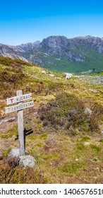 A sign leading to Kjerag and Langavatn, Norway. Sign is located in a hiking trail, marking the right way for the hikers. In the back massive mountain range. Bright and sunny day, perfect for a trek