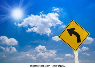 Sign- left turn warning on blue sky background