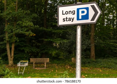 Sign: Long stay parking, with a bench and a shopping trolley in the background, seen in Crowborough, East Sussex, England, UK