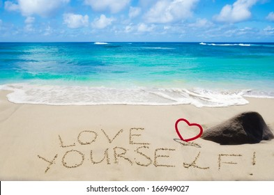 "Sign ""Love yourself"" with heart on the sandy beach by the ocean"