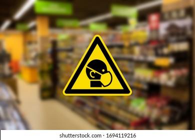 Zeichen maskiert Mann auf unscharfem Foto von Supermarkt. einen Mann in einer medizinischen Maske am Eingang zum Supermarkt während des Ausbruchs des Coronavirus Covid-19 zu unterzeichnen. maskierter Eingang in den Supermarkt.