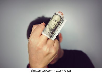 sign middle finger money hundred dollars bill man in a black t-shirt neutral grey background. contempt for money, corruption, venality, corruptibility, bribability