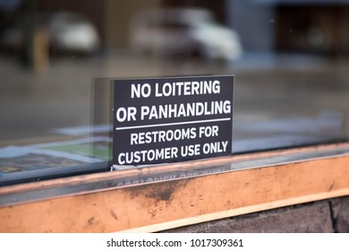 Sign for no loitering or panhandling on the glass window of a store