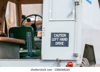 Sign on the back of an old Landrover warning following motorists that it is left-hand drive.