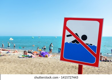 A sign on the beach is not allowed to swim! People bathe and rest on the sea in spite of the sign and ban.
