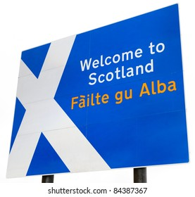 """A sign on the border crossing to Scotland from England.  Contains the Scottish flag and """"Welcome to Scotland"""" in English and Gaelic.  Isolated on a white background."""