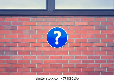 Sign on a brick wall with a question mark.
