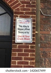 Sign on brick wall warning pedestrians that the sidewalk could be slippery when icy or snowy.  Rectangular sign in white with red and black lettering.