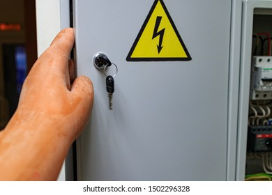 the sign on the door gently with electricity and hand in glove dielectric opens the door. work in protective gloves in electrical networks