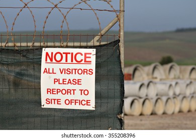A sign on the fence of a construction site instructs visitors to report to the site office.